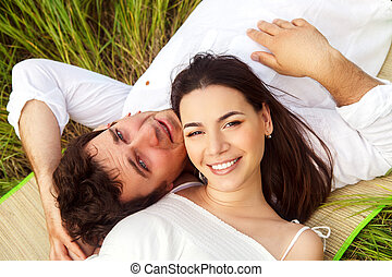 Happy young smiling couple on the summer meadow outdoors