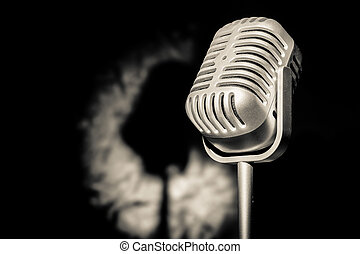 Silver retro microphone in spot light with shadow backdrop