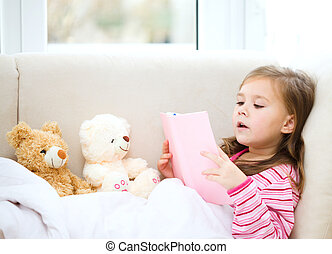 Little girl is reading a story for her teddy bears while...