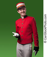 Portrait of a concierge (porter) in a red jacket on a green...