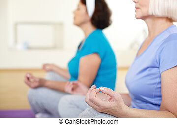 Spiritual balance - Close-up of aged female doing yoga...