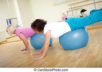 Exercising - Portrait of sporty females doing physical...