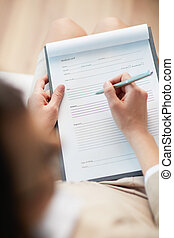 Medical record - Female counselor writing down some...