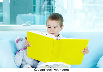 Little reader - Boy reading interesting book at leisure