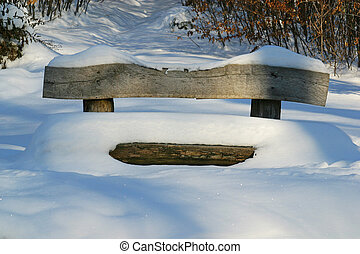 Wooden bench covered with snow