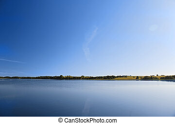 calm water of lake, woods on other side and blue sky...