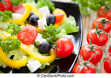 salad with fresh vegetables on a black plate