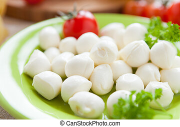 small balls of mozzarella on green plate, closeup