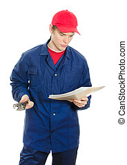 Young male plumber in uniform with wrench reading manual. Isolated on white