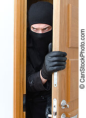 Male burglar in mask breaking into the house