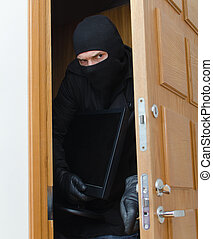 Male burglar in mask breaking into the house and stealing monitor