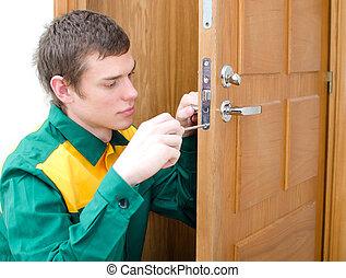 Young handyman in uniform changing door lock