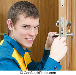 Smiling handyman in uniform changing door lock
