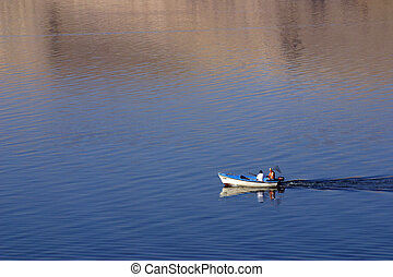 Fisherman in boat sailing out
