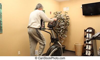 man exercising - mature man working out on an elliptical...