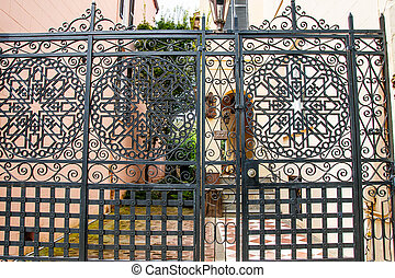 Ornamental Black Iron Gate on House - A large ornamental...
