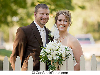 Bride and Groom Behind a White Picket Fence