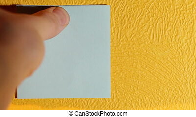 Hand sticks pink sticker on the yellow wall. - Hand sticks...