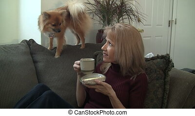 Woman drinking tea with dog