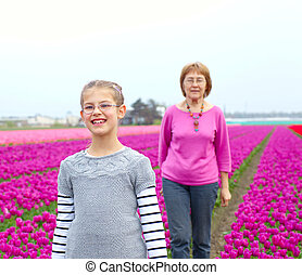 Girl with grandmother in the purple tulips field