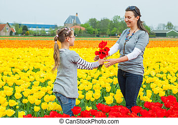 Girl with mother in the tulips field