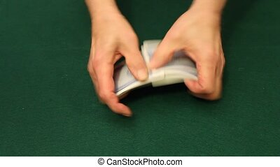 shuffling cards - shuffling a deck of cards over a green...