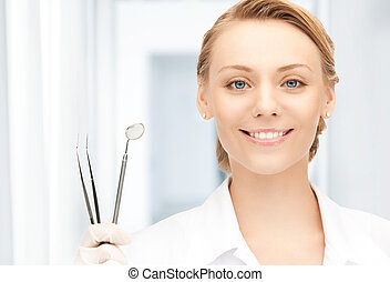 dentist with tools - picture of attractive female dentist...