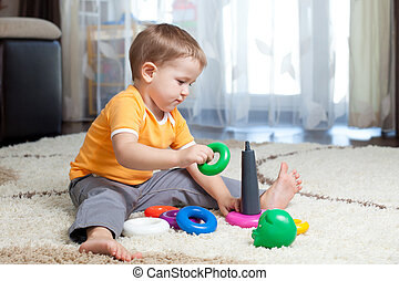 Child boy playing with toy at home.