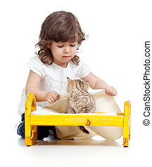 curly child girl playing with kitten as mother with baby -...