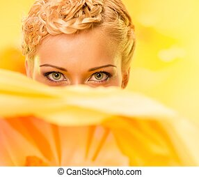 Beautiful young woman hiding behind big yellow flower