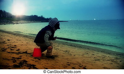 Little boy on the beach sitting on a red bucket