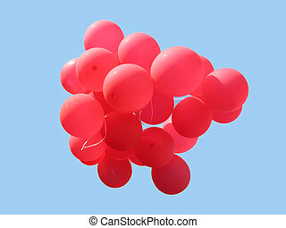 Bunch of red party balloons against blue sky