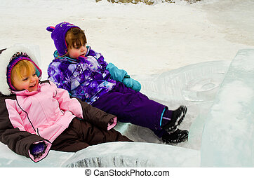 Fun in the snow - Two toddlers kicking back in the snow