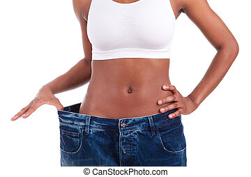 Young african woman in old jeans pant after losing weight...