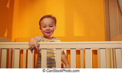 Boy smiling in playpen.