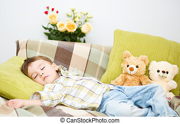 Cute little boy is sleeping next to his teddy bears