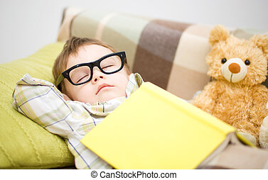 Cute little boy is sleeping in front of his teddy bears...