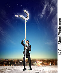 Image of businessman climbing rope attached to question sign...