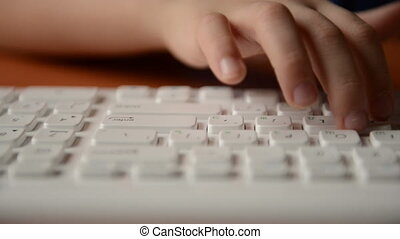 Child typing on a keyboard. Close v