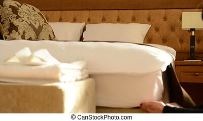 housemaid covers a bed. Dolly shot