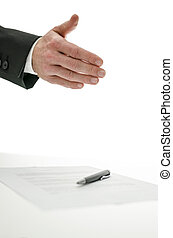 Business man offering a handshake over a signed contract....