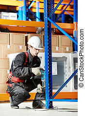 warehouse worker installing rack arrangement - One warehouse...