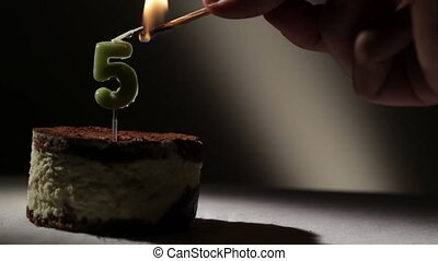 Candle five in tiramisu cake. Birthday vintage background.