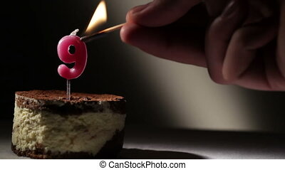 Candle nine in tiramisu cake. Birthday vintage background.