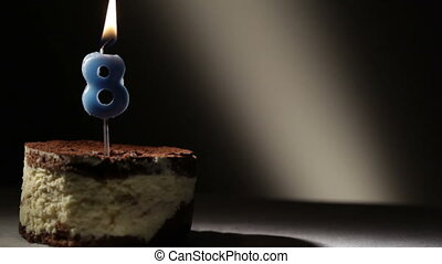 Candle eight in tiramisu cake. Birthday vintage background.