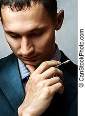 businessman with pen thinking