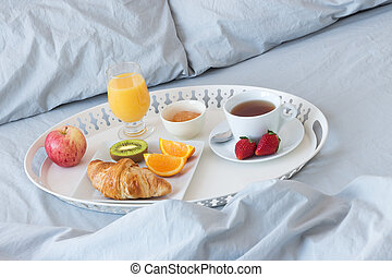 Tray with healthy breakfast on a bed