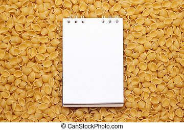 blank notepad on uncooked macaroni background - white blank...
