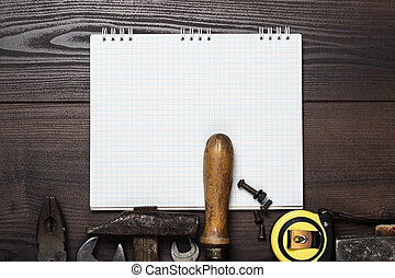 construction tools and notepad on wooden background -...