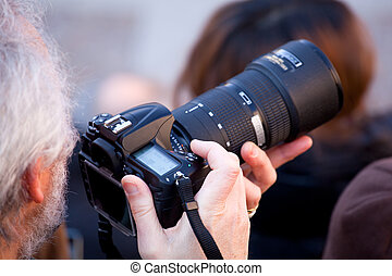 Photographer taking a photo with DSLR camera